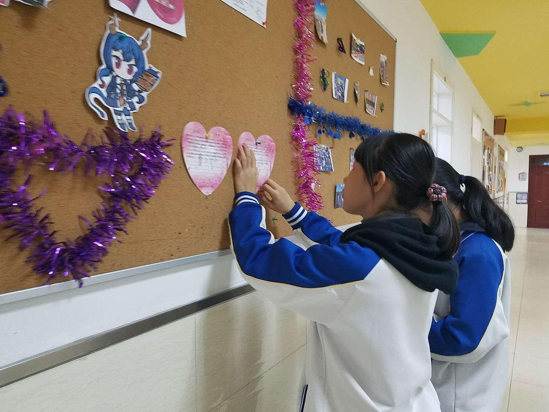 学生们将 爱心卡粘贴在班级扎板上。.jpg